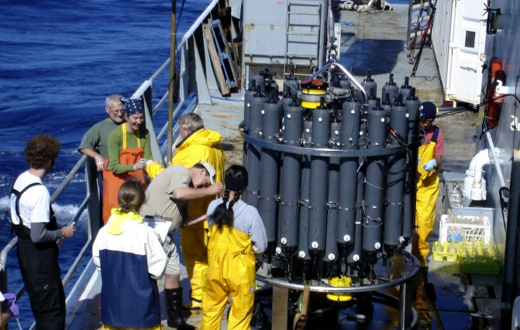 Scientists collecting samples from a CTD (Conductivity-Temperature-Depth) rosette.