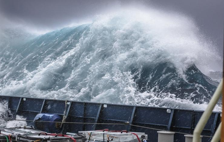 View of a storm from a research vessel. The wave height is significantly taller than the railing on the research vessel.