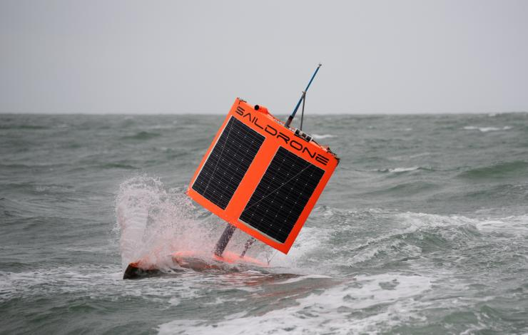 Orange autonomous vehiclewith a square wing in stormy water conditions