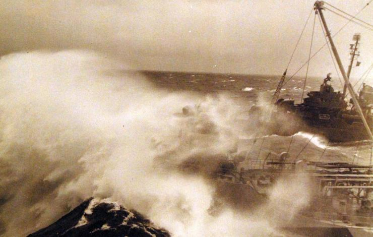 Sepia image of a ship and a destroyer encountering a large wave sweeping past the oiler's bow