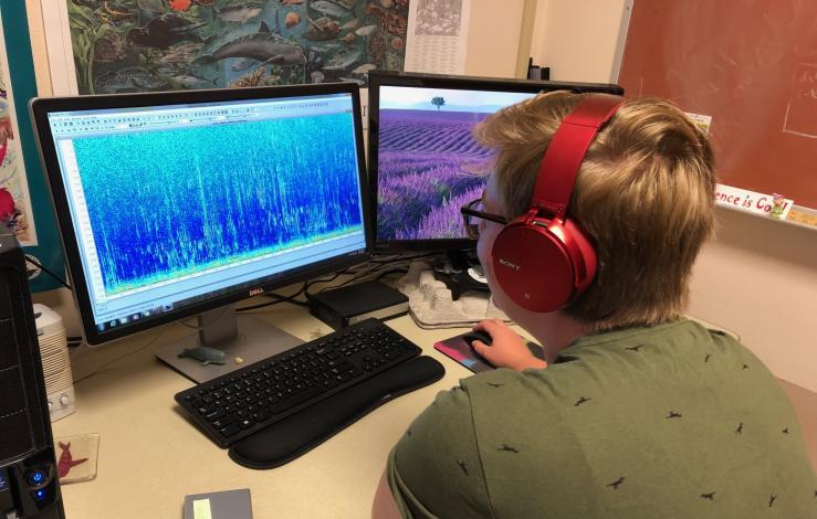 A master's student sitting in front of a computer looking at sound spectrogram on a computer from
