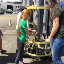 Middle school students taking samples from a CTD Rosette during camp