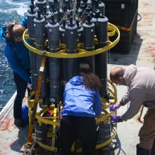 People stand around a circular CTD instrument collecting water samples on a ship out in the Pacific Ocean