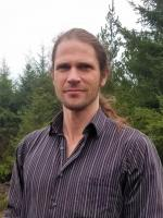 Anson standing in front of conifer trees in a dark purple collared button up shirt
