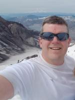Rusy smiling with white t-shirt and sunglasses on in front of mountain view behind