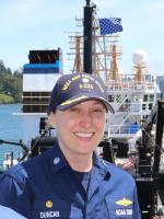 Sarah smiling in blue NOAA Corps uniform with blue hat on in front of a NOAA Ship